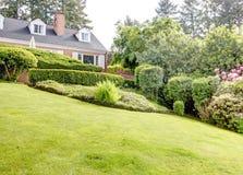 Κόκκινο σπίτι τούβλου με τον αγγλικό κήπο και τα άσπρα παραθυρόφυλλα παραθύρων. Στοκ φωτογραφίες με δικαίωμα ελεύθερης χρήσης