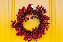 Κόκκινο στεφάνι διακοπών μούρων στην κίτρινη πόρτα Στοκ Εικόνα