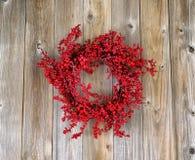Κόκκινο στεφάνι μούρων ελαιόπρινου στους ηλικίας ξύλινους πίνακες Στοκ φωτογραφία με δικαίωμα ελεύθερης χρήσης