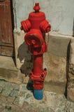 Κόκκινο στόμιο υδροληψίας δίπλα στον τοίχο ασβεστοκονιάματος στοκ φωτογραφίες