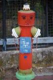 Κόκκινο στόμιο υδροληψίας με το πρόσωπο αστείο στόμιο υδροληψίας, φράκτης κήπων ως backgrou Στοκ φωτογραφία με δικαίωμα ελεύθερης χρήσης