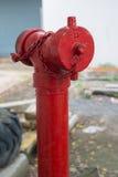 Κόκκινο στόμιο υδροληψίας πυρκαγιάς στην άκρη του δρόμου πόλεων Στοκ Εικόνα