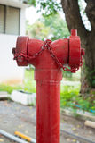 Κόκκινο στόμιο υδροληψίας πυρκαγιάς στην άκρη του δρόμου πόλεων Στοκ Εικόνες