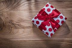 Κόκκινο συσκευασμένο παρόν γενεθλίων στην ξύλινη έννοια εορτασμών πινάκων στοκ εικόνες