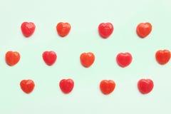 Κόκκινο σχέδιο καραμελών καρδιών ημέρας βαλεντίνων ` s στο πράσινο υπόβαθρο χρώματος εγγράφου κρητιδογραφιών άνδρας αγάπης φιλιών στοκ εικόνες