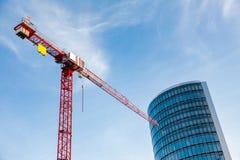 Κόκκινο σύγχρονο κτήριο οικοδόμησης γερανών πύργων Στοκ Εικόνες