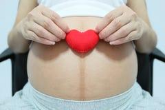 Κόκκινο σύμβολο καρδιών υπό εξέταση ασιατικές γυναίκες έγκυες Στοκ Εικόνες