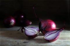 Κόκκινο σύνολο κρεμμυδιών και διχοτομημένος στο αγροτικό σκοτεινό ξύλο στοκ φωτογραφία με δικαίωμα ελεύθερης χρήσης