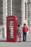 Κόκκινο τηλεφωνικό κιβώτιο και ένας περίεργος τουρίστας στοκ εικόνες με δικαίωμα ελεύθερης χρήσης