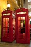 Κόκκινο τηλεφωνικό κιβώτιο συμβόλων του Λονδίνου στη φωτισμένη οδό Στοκ Εικόνα