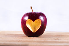 Κόκκινο της Apple με την καρδιά στον ξύλινο τεμαχίζοντας πίνακα Στοκ εικόνα με δικαίωμα ελεύθερης χρήσης