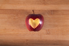 Κόκκινο της Apple με την καρδιά στον ξύλινο τεμαχίζοντας πίνακα Στοκ φωτογραφία με δικαίωμα ελεύθερης χρήσης