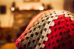 Κόκκινο τονισμένο κάλυμμα τσιγγελακιών στο πίσω μέρος ενός καναπέ σε ένα οικογενειακό δωμάτιο στοκ φωτογραφία