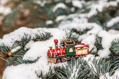 Κόκκινο τραίνο παιχνιδιών Χριστουγέννων στο χιονώδες έλατο κλάδων Στοκ φωτογραφία με δικαίωμα ελεύθερης χρήσης