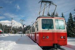 Κόκκινο τραίνο στο σταθμό βουνών το χειμώνα Στοκ Φωτογραφίες
