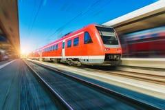 Κόκκινο τραίνο υψηλής ταχύτητας στην κίνηση στο σιδηροδρομικό σταθμό στοκ εικόνα