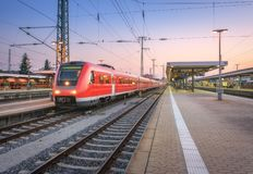 Κόκκινο τραίνο υψηλής ταχύτητας στο σιδηροδρομικό σταθμό στο σούρουπο στοκ εικόνα με δικαίωμα ελεύθερης χρήσης