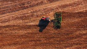 Κόκκινο τρακτέρ καμπινών που οργώνει τον τομέα με το πράσινο άροτρο, εναέρια άποψη φιλμ μικρού μήκους