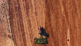 Κόκκινο τρακτέρ καμπινών που οργώνει τον τομέα με το πράσινο άροτρο, εναέρια άποψη απόθεμα βίντεο