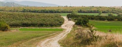 Κόκκινο τρακτέρ στο δρόμο στην πλευρά χωρών οπωρώνας φύλλων καρπών κλάδων μήλων μήλων στοκ φωτογραφίες