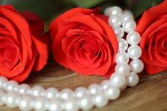 Κόκκινο τριών λουλουδιών τριαντάφυλλων με τις χάντρες μαργαριταριών στην ξύλινη κινηματογράφηση σε πρώτο πλάνο υποβάθρου στοκ εικόνες