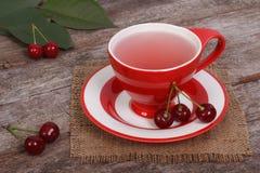 Κόκκινο τσάι κερασιών σε ένα φλυτζάνι και φρέσκα κεράσια Στοκ Εικόνες