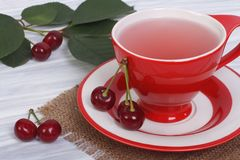 Κόκκινο τσάι κερασιών σε ένα φλυτζάνι και φρέσκα κεράσια Στοκ εικόνες με δικαίωμα ελεύθερης χρήσης