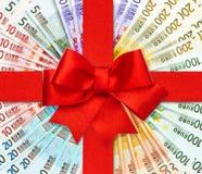 Κόκκινο τόξο κορδελλών δώρων πέρα από τα ευρο- τραπεζογραμμάτια Στοκ Φωτογραφία