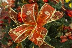 Κόκκινο τόξο κορδελλών στον πράσινο κλάδο δέντρων έλατου Στενή φωτογραφία διακοσμήσεων χριστουγεννιάτικων δέντρων με τη θέση κειμ Στοκ Εικόνες