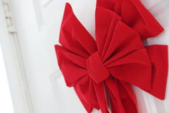 Κόκκινο τόξο Χριστουγέννων στην πόρτα Στοκ εικόνες με δικαίωμα ελεύθερης χρήσης