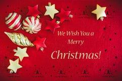 Κόκκινο υπόβαθρο καρτών Χριστουγέννων με τις χρυσά διακοσμήσεις, τις σφαίρες και τα αστέρια, και την επιθυμία του κειμένου στοκ φωτογραφία