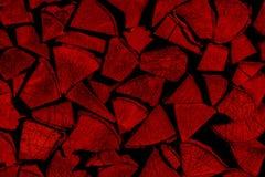 Κόκκινο υπόβαθρο καυσόξυλου που συσσωρεύεται σε έναν woodpile στοκ εικόνες