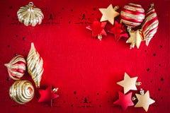 Κόκκινο υπόβαθρο Χριστουγέννων με τα χρυσές αστέρια και τις διακοσμήσεις κορδελλών, με το διάστημα αντιγράφων για το κείμενό σας στοκ εικόνα