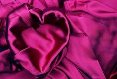 Κόκκινο υλικό σατέν με την έννοια αγάπης μορφής καρδιών Στοκ Εικόνες