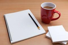 Κόκκινο φλυτζάνι καφέ με τη σημείωση της Λευκής Βίβλου και μολύβι στην επιχείρηση tabl Στοκ Εικόνες