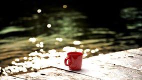 Κόκκινο φλυτζάνι καφέ στο ξύλινο πάτωμα του συνόλου ελεύθερη απεικόνιση δικαιώματος