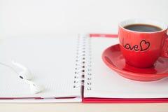 Κόκκινο φλυτζάνι καφέ στο σημειωματάριο, ημέρα βαλεντίνων ` s Στοκ Φωτογραφίες