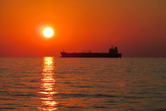 Κόκκινο φως ηλιοβασιλέματος επάνω από τη θάλασσα, σκιαγραφία σκαφών Στοκ Φωτογραφία