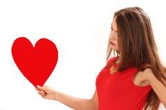 Κόκκινο φόρεμα με την κάρτα ημέρας του κόκκινου βαλεντίνου καρδιών στα χέρια στοκ φωτογραφίες