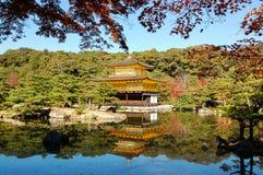 Κόκκινο φύλλο με το χρυσό περίπτερο στο Κιότο Στοκ Φωτογραφίες