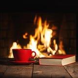 Κόκκινο φλιτζάνι του καφέ ή τσάι και παλαιό βιβλίο στον ξύλινο πίνακα κοντά στην πυρκαγιά Στοκ εικόνα με δικαίωμα ελεύθερης χρήσης