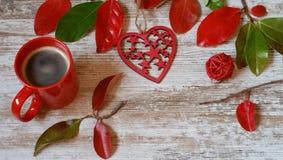 Κόκκινο φλιτζάνι του καφέ, κόκκινα καρδιά και φύλλα φθινοπώρου στο ξύλινο υπόβαθρο Στοκ Φωτογραφία