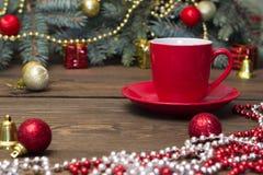 Κόκκινο φλιτζάνι του καφέ με τα παιχνίδια Χριστουγέννων Στοκ Φωτογραφίες