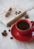 Κόκκινο φλιτζάνι του καφέ με την κανέλα φασολιών και καρυκευμάτων καφέ στοκ εικόνες