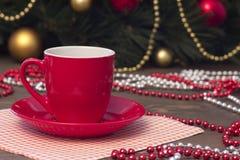 Κόκκινο φλιτζάνι του καφέ, παιχνίδια Χριστουγέννων και χάντρες Στοκ Φωτογραφία