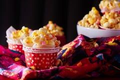 Κόκκινο φλυτζάνι εγγράφου με popcorn στο μαύρο κλίμα Στοκ εικόνα με δικαίωμα ελεύθερης χρήσης