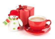 Κόκκινο φλυτζάνι καφέ, κιβώτιο δώρων και παιχνίδι χιονανθρώπων Στοκ Φωτογραφίες