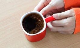 Κόκκινο φλυτζάνι καφέ με τη φυσαλίδα στο χέρι γυναικών στον ξύλινο πίνακα Στοκ φωτογραφίες με δικαίωμα ελεύθερης χρήσης