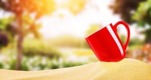 Κόκκινο φλυτζάνι καφέ στην άμμο παραλιών πέρα από τη μουτζουρωμένη φύση κήπων λουλουδιών Στοκ φωτογραφία με δικαίωμα ελεύθερης χρήσης