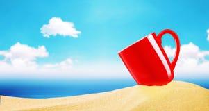 Κόκκινο φλυτζάνι καφέ στην άμμο παραλιών πέρα από το μουτζουρωμένο μπλε ουρανό με τα σύννεφα Στοκ Εικόνες